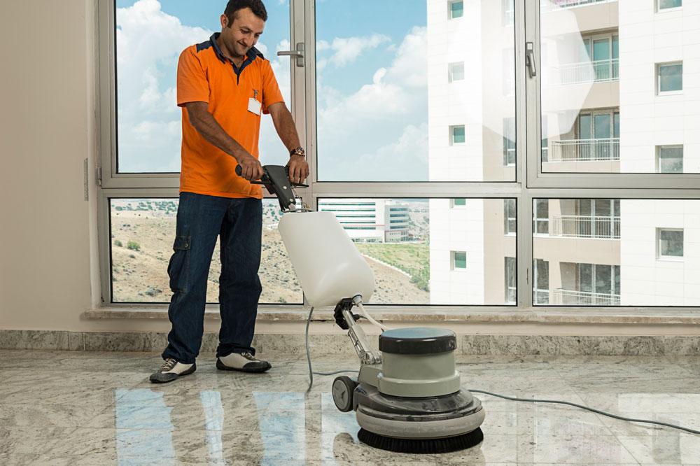 Profesional realizando pulido del suelo en un edificio de viviendas